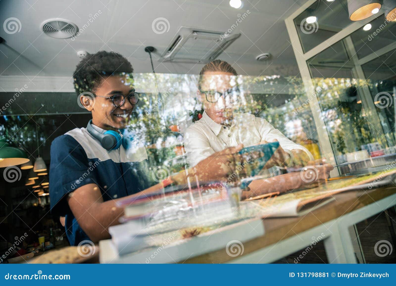 坐与他的老师的快乐的正面学生