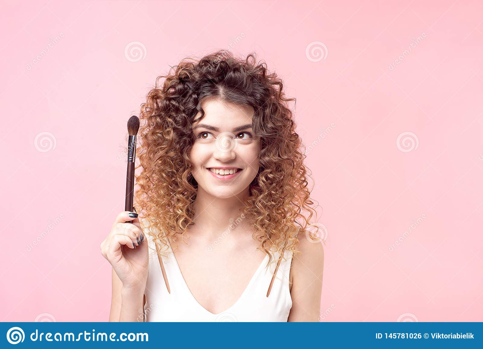 坐与构成刷子的快乐的愉快的妇女,当工作在发廊时