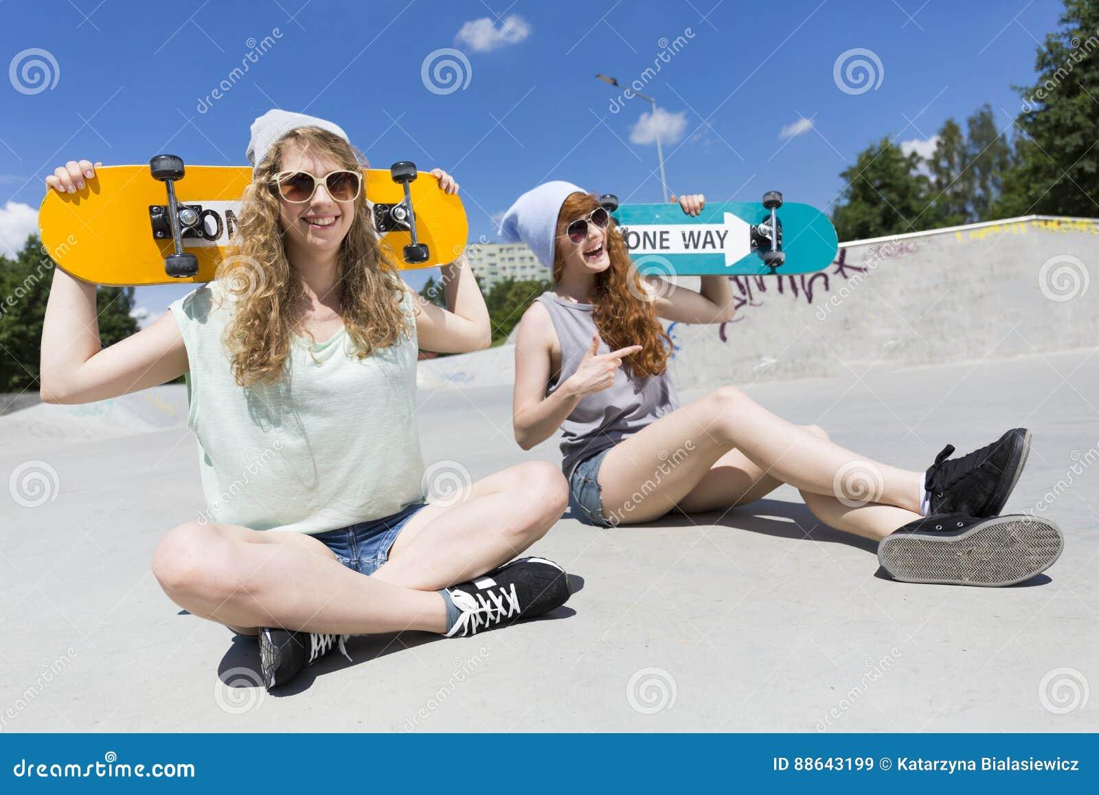 坐与他们的滑板的女孩