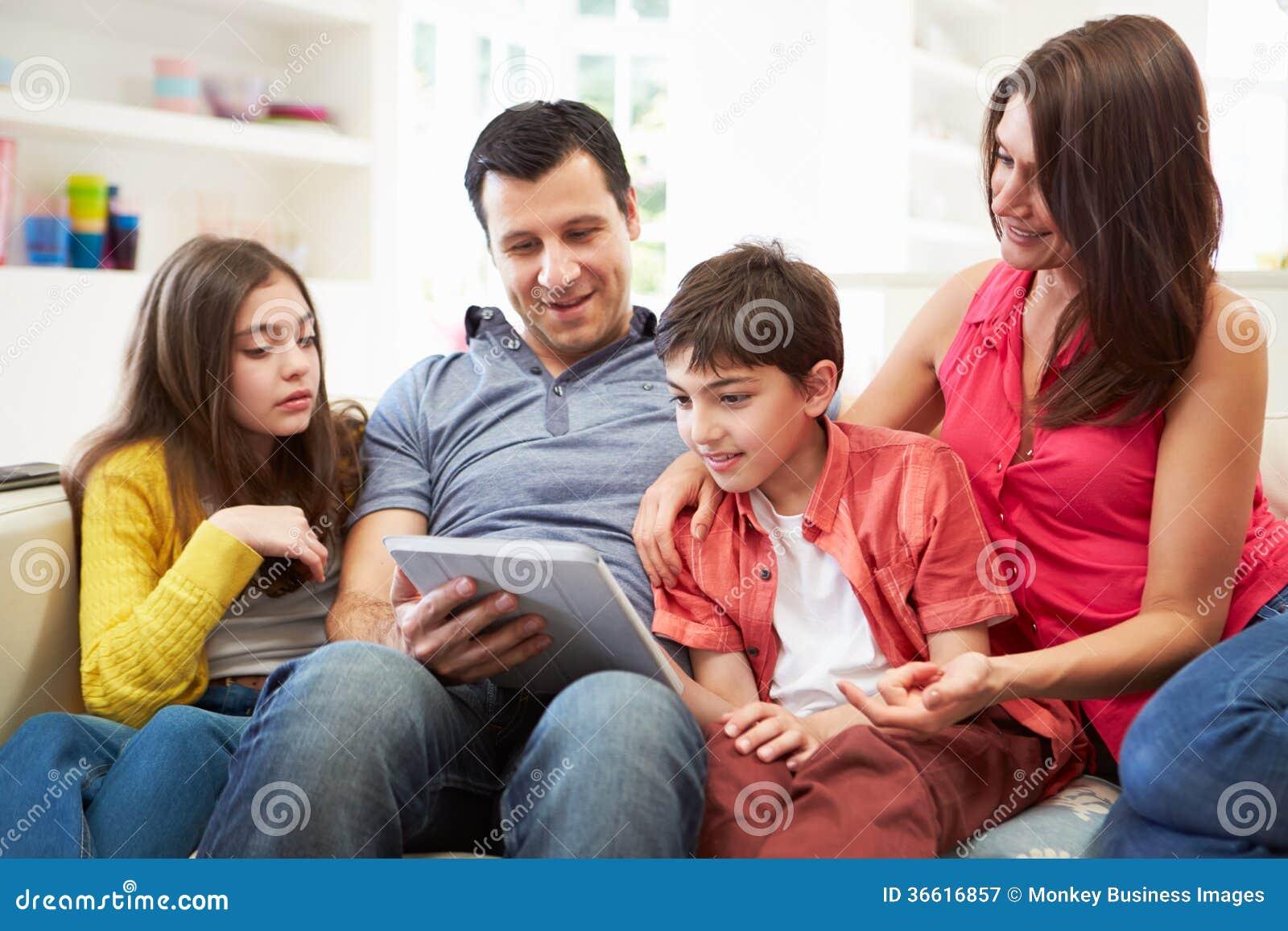 坐使用数字式片剂的西班牙家庭