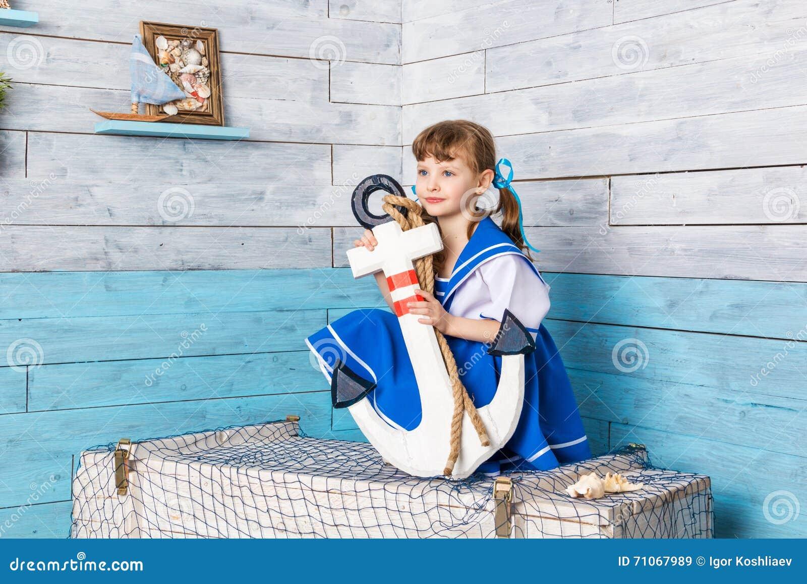 坐和拿着船锚的小女孩