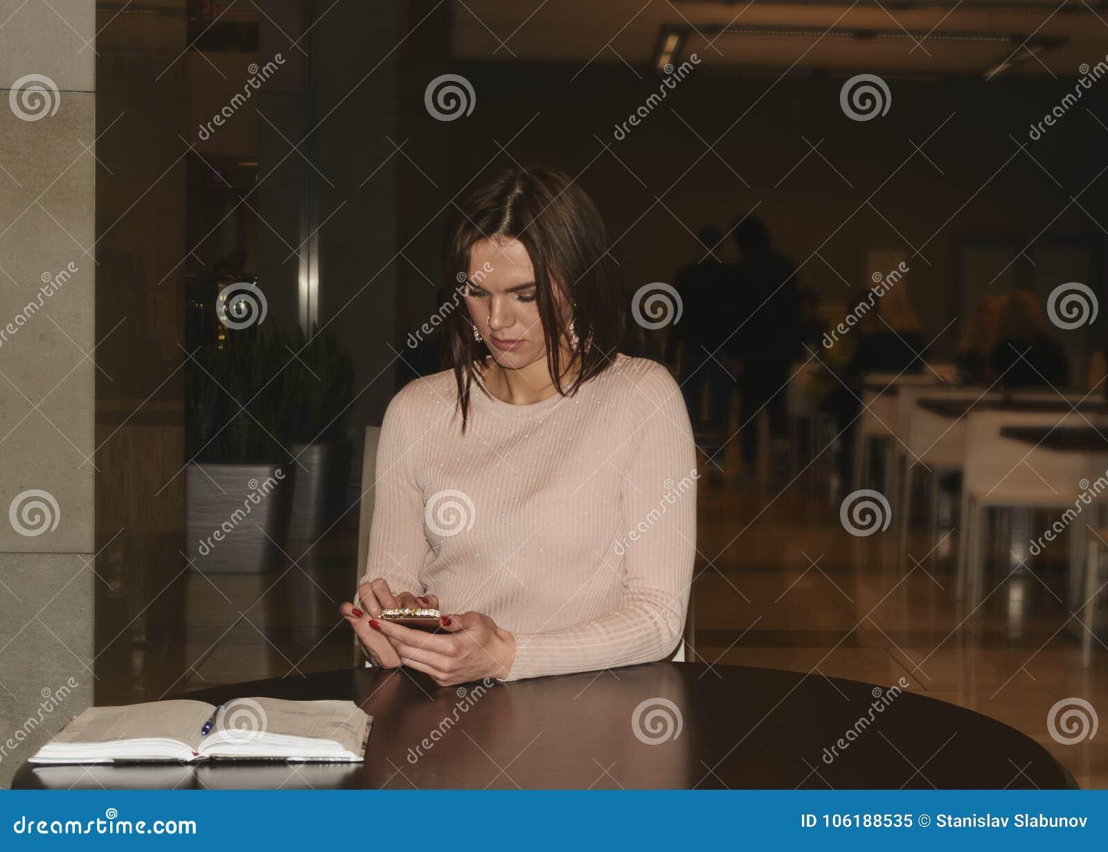 坐在一张圆的木桌上的美丽的年轻深色的妇女