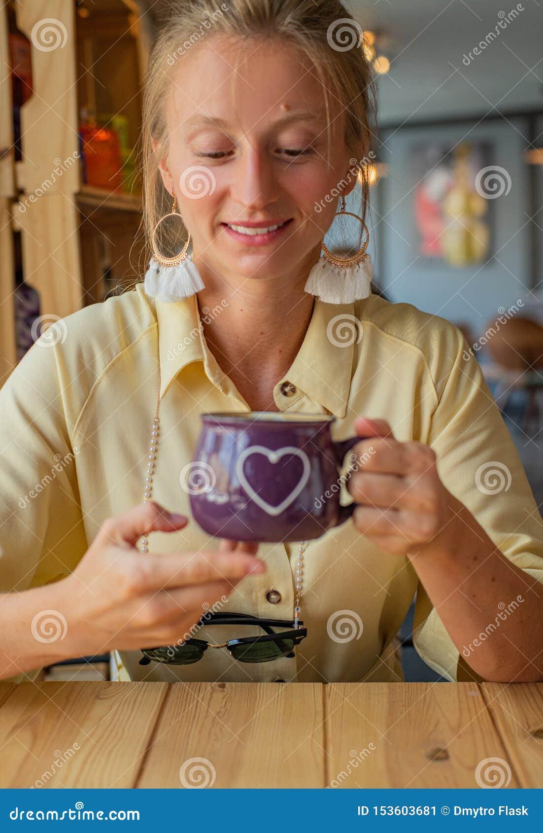 坐在与一杯咖啡的一个咖啡馆的美女 可爱的年轻女人喝咖啡或热奶咖啡