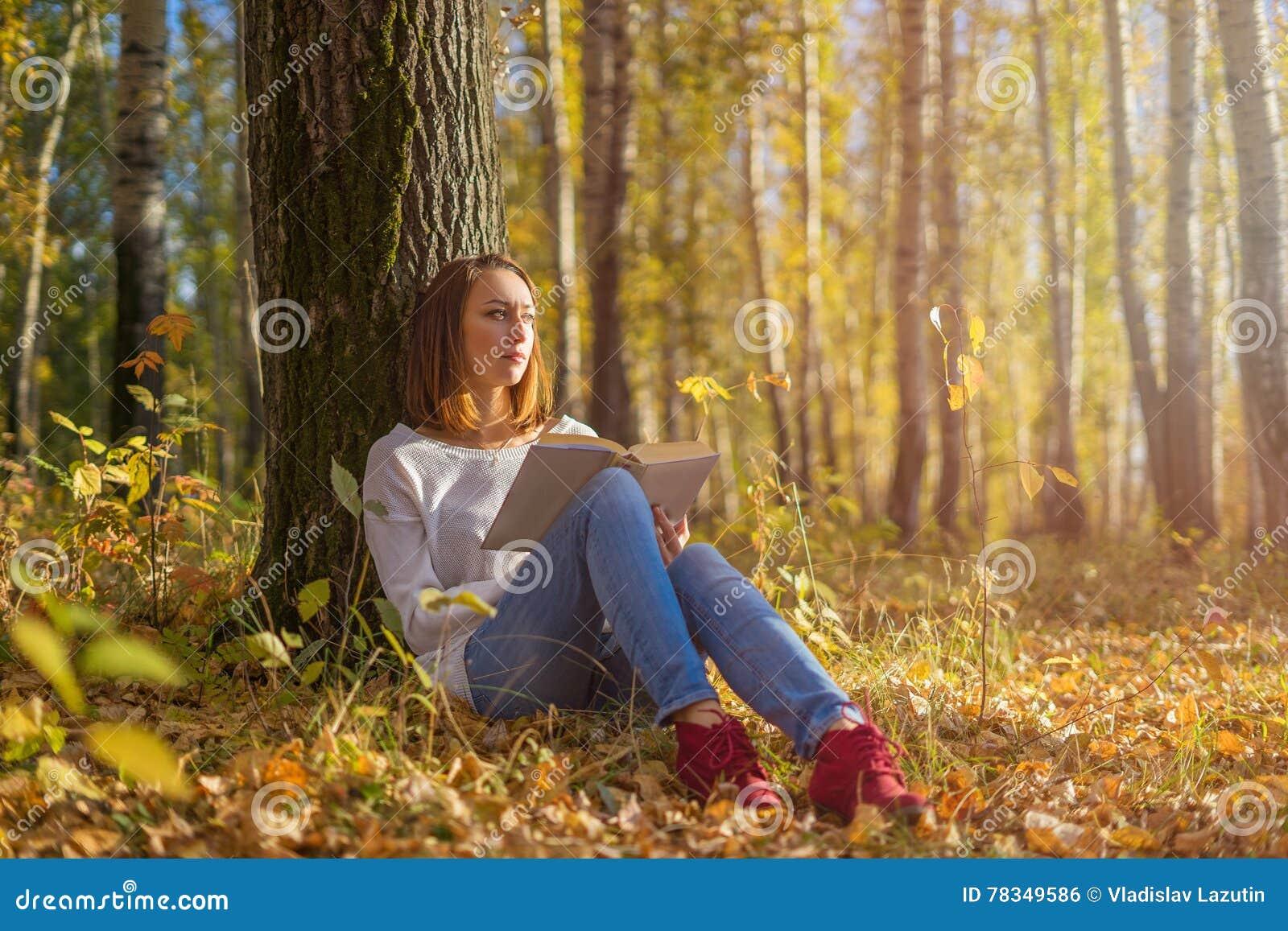坐在与书的一棵树下的女孩
