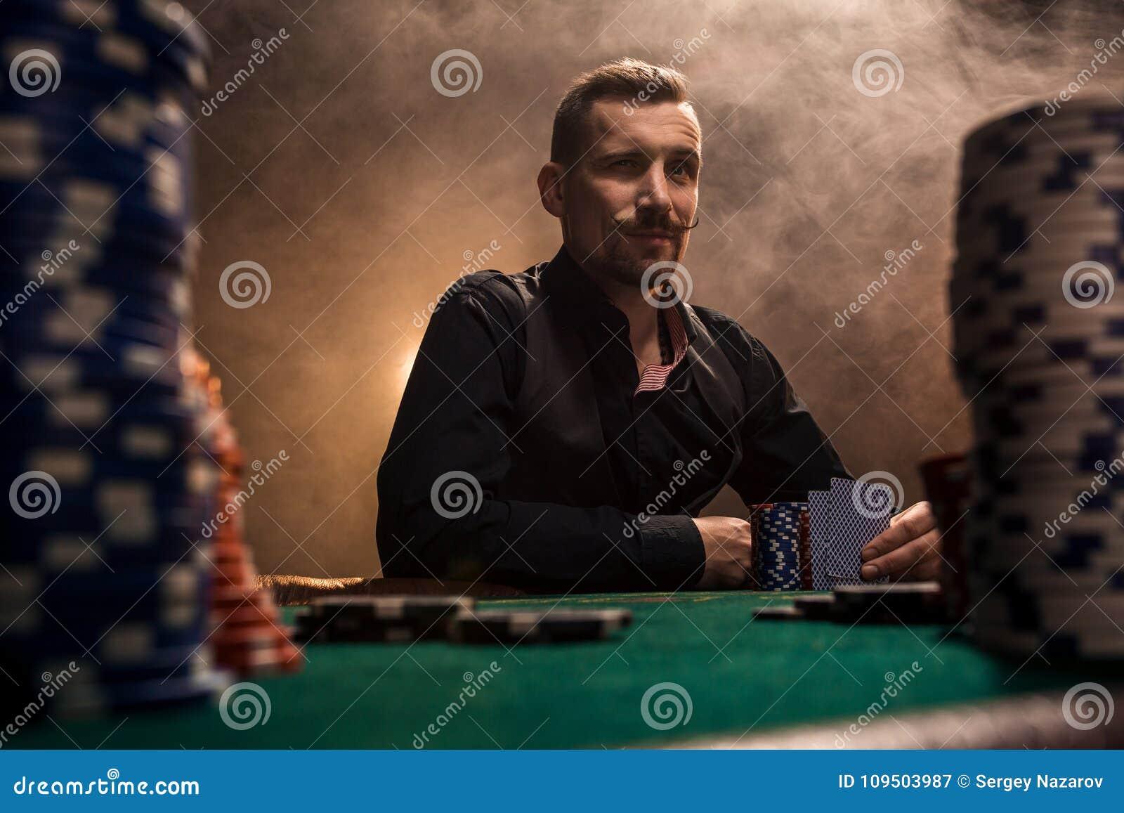 坐在与卡片和芯片的啤牌桌后的年轻英俊的人