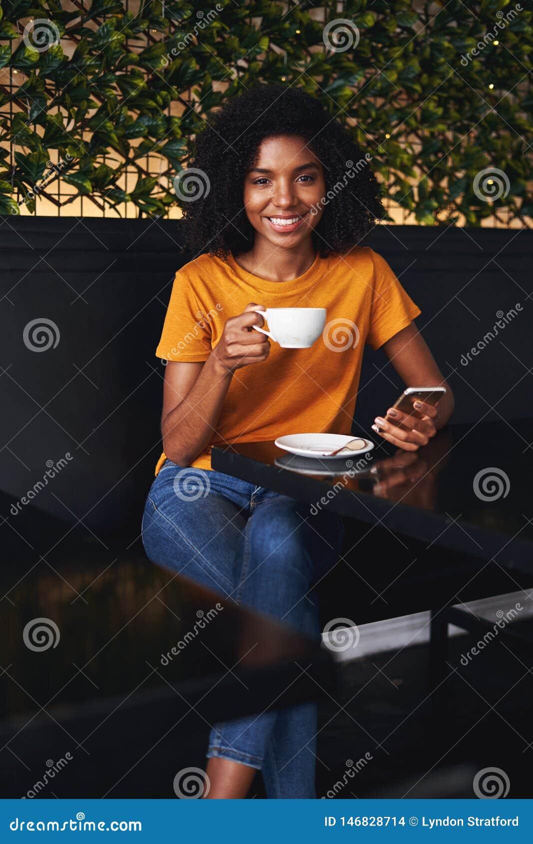 坐在与智能手机的咖啡馆的年轻女人的画象