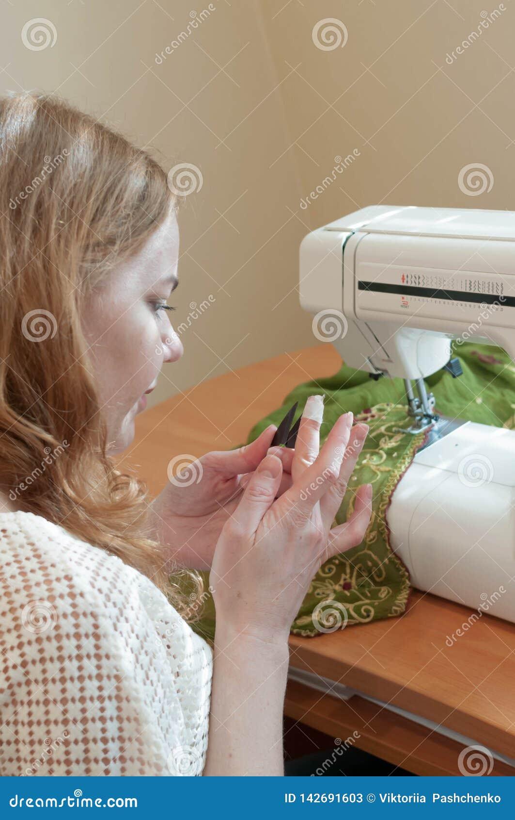 坐在与缝纫机的桌上和看受伤的手指的裁缝
