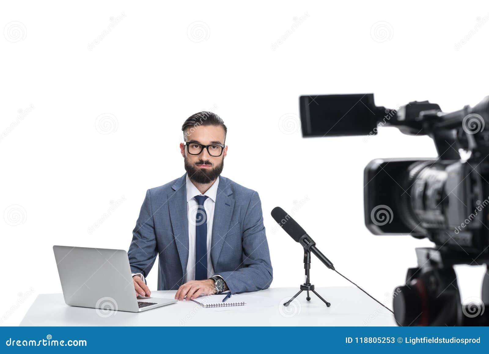 坐在与膝上型计算机、笔记薄和话筒的桌上和看照相机的男性新闻广播员,