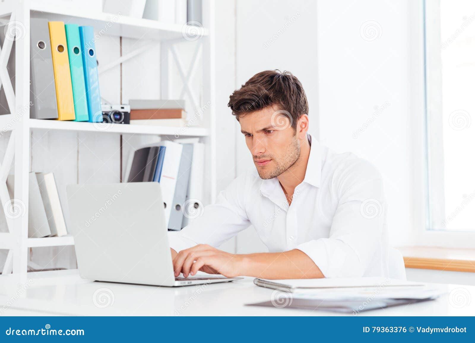 坐在与膝上型计算机的桌上的年轻周道的英俊的商人