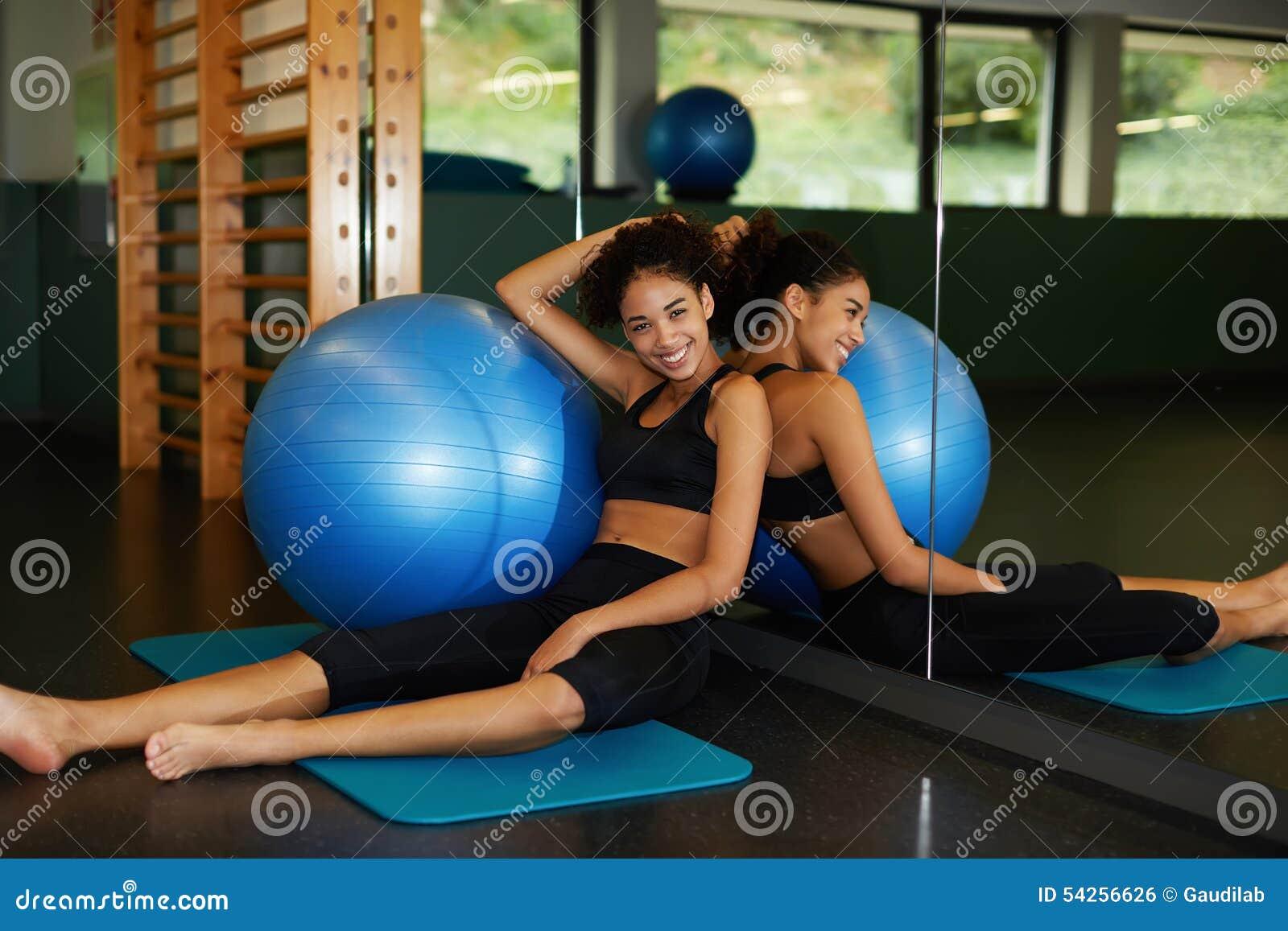 坐在与适合球的健身房的愉快和美丽的少妇