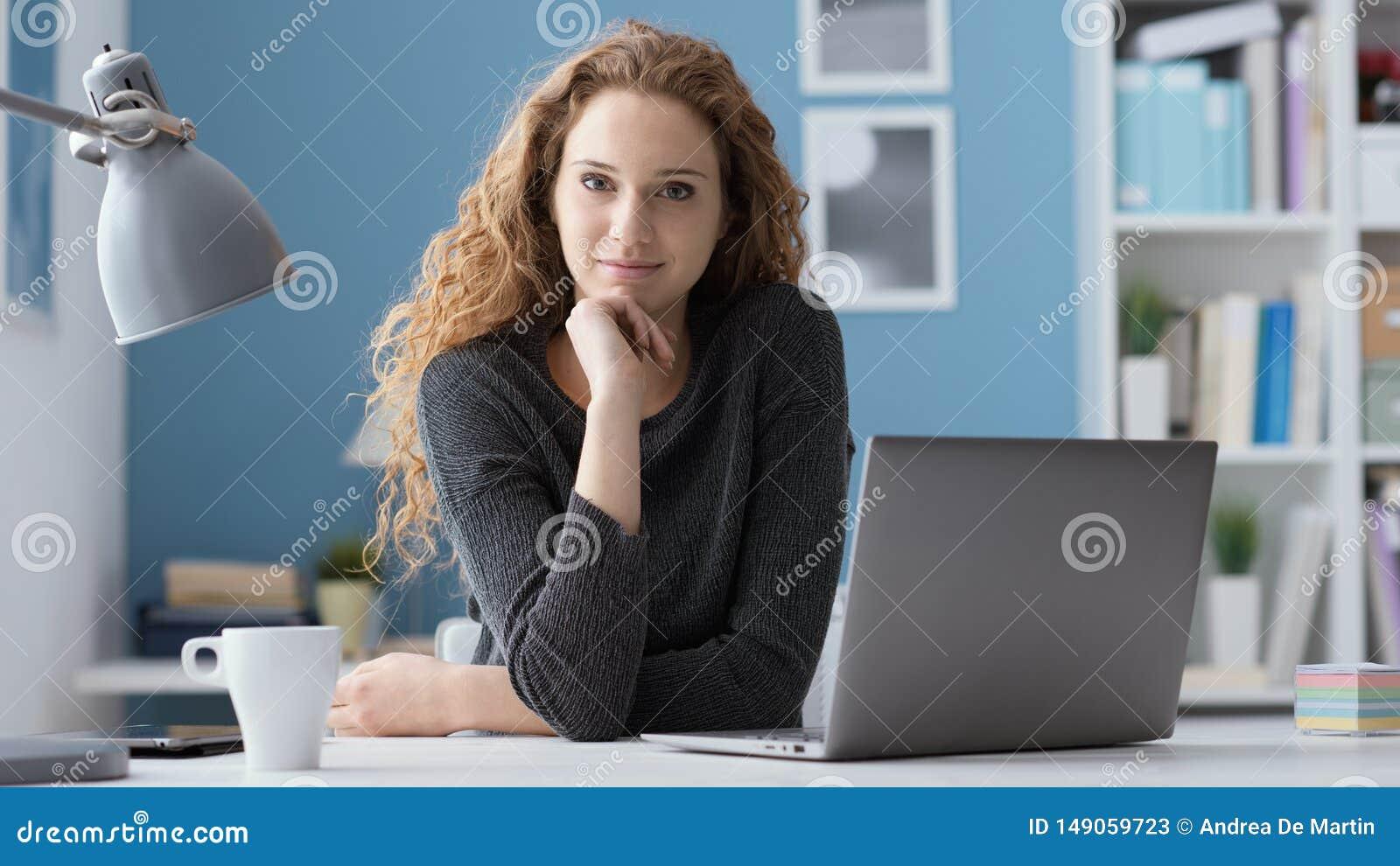 坐在书桌和摆在的年轻女人