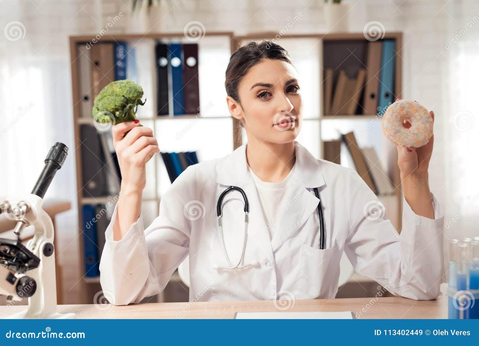 坐在书桌的女性医生在有显微镜和听诊器的办公室 妇女拿着硬花甘蓝和多福饼