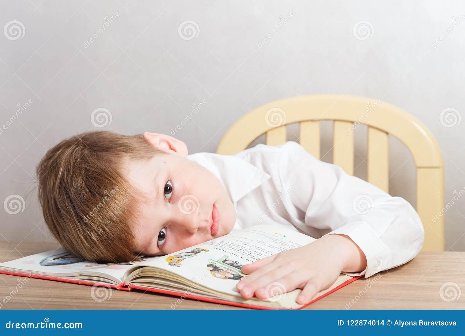 坐在书桌的白色衬衣的哀伤的疲乏的男孩