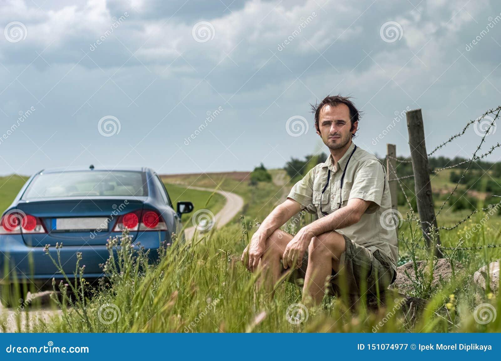 坐在他的蓝色汽车附近的年轻旅客在乡下