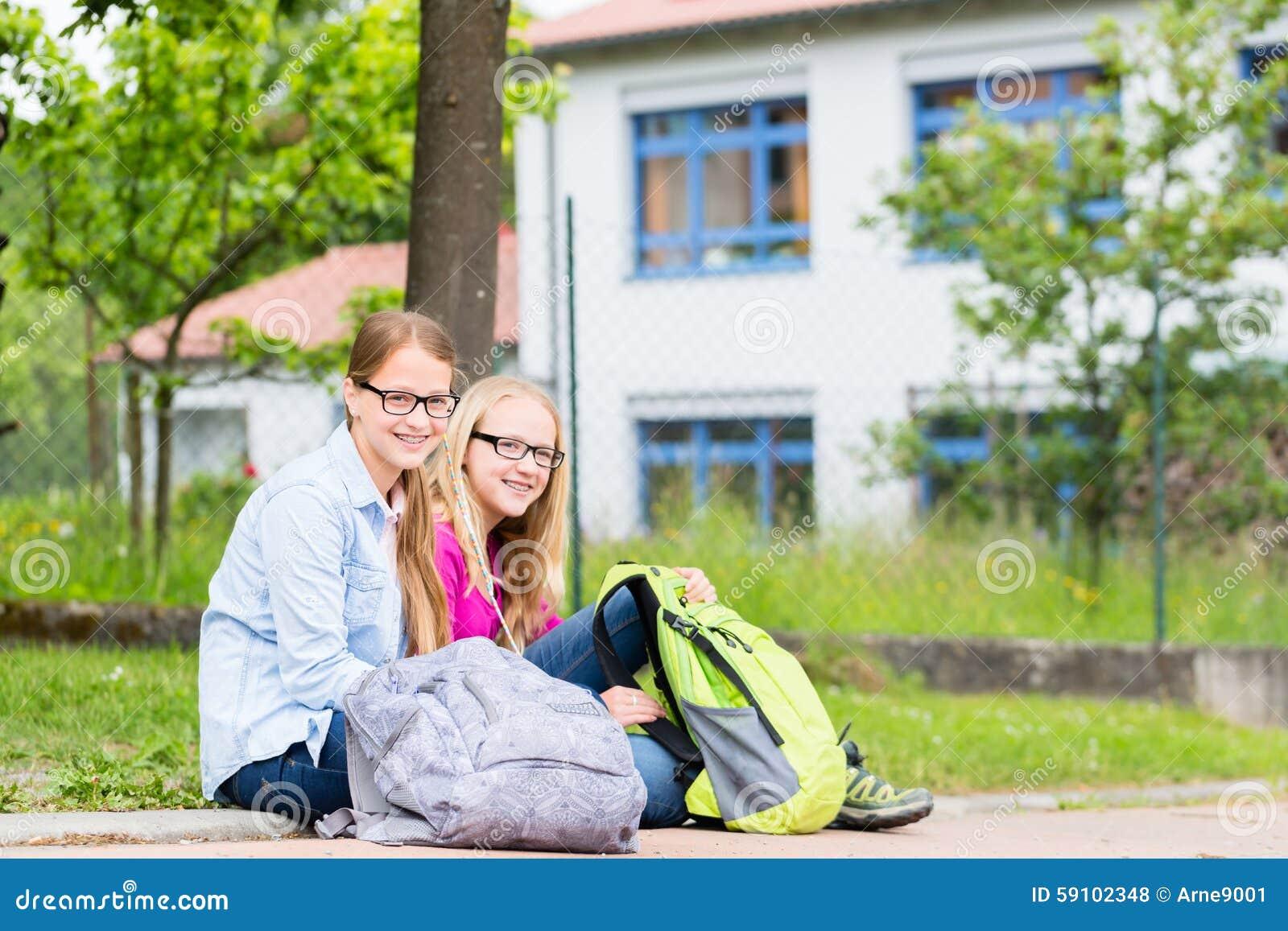 坐在凹进处的学校的两名学生