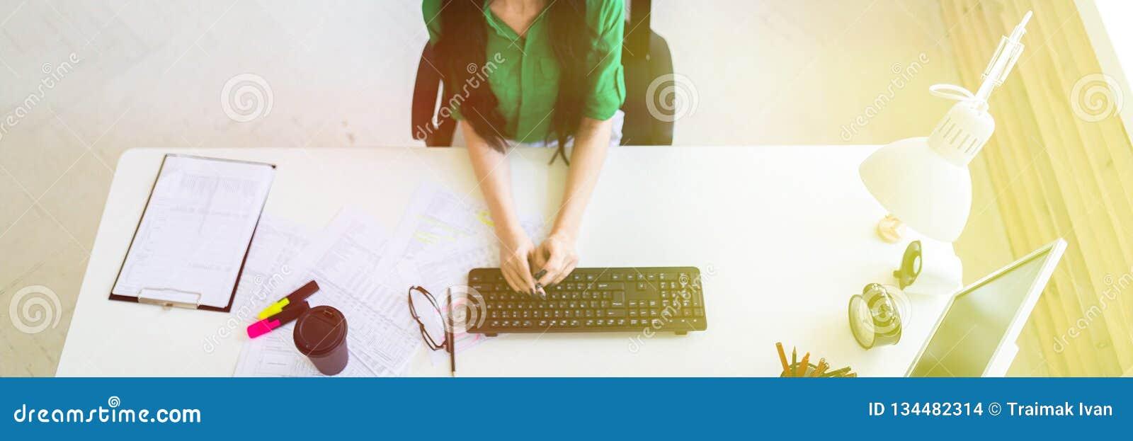 坐在办公桌和键入在键盘的一个女孩的顶视图