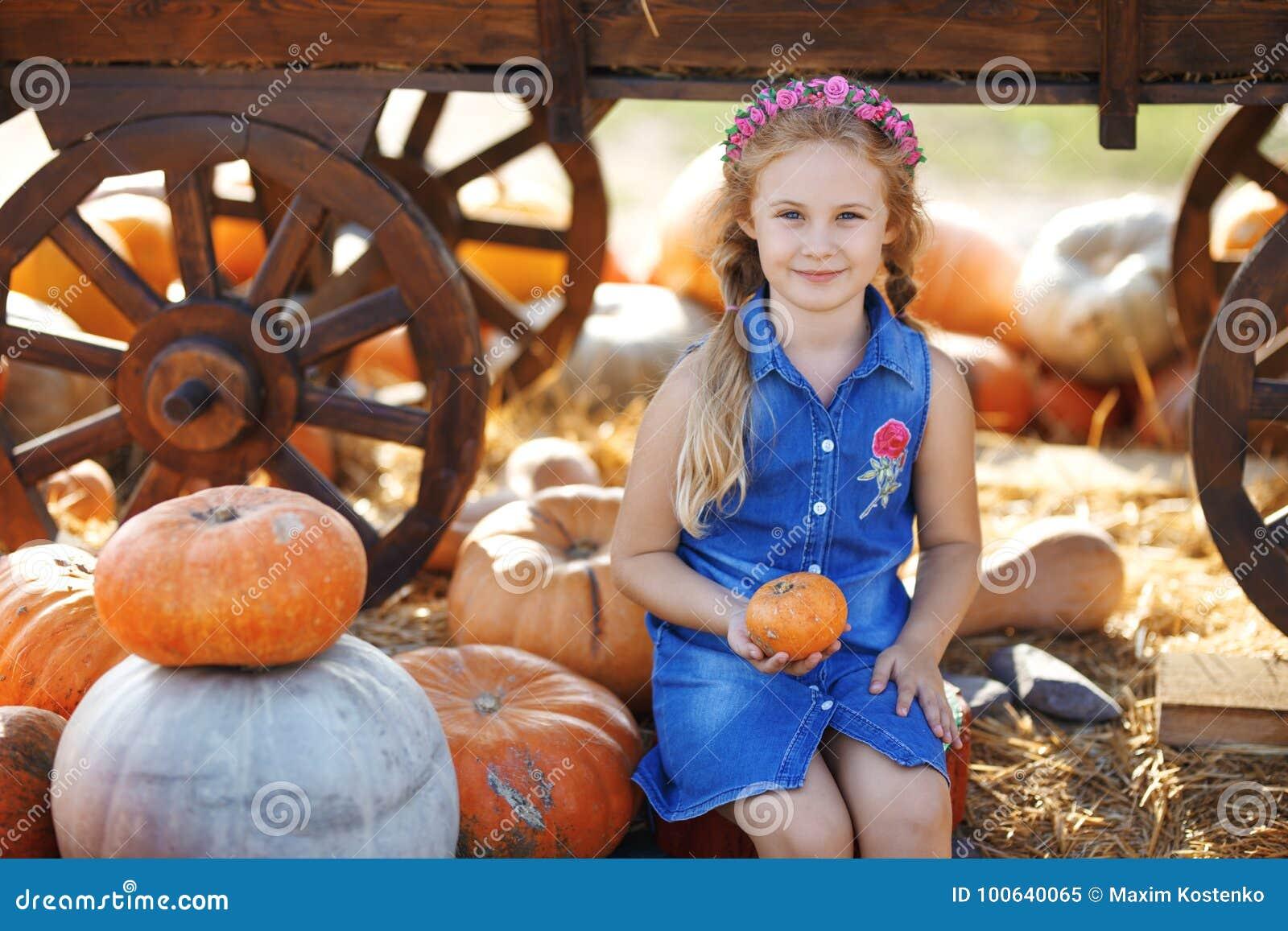 坐在南瓜之间的愉快的学校女孩在地方农夫市场上在晴朗的秋天天