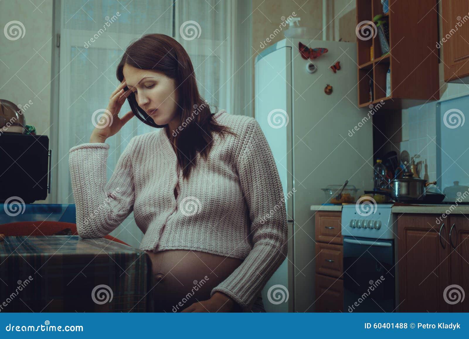 坐在厨房里的哀伤的孕妇