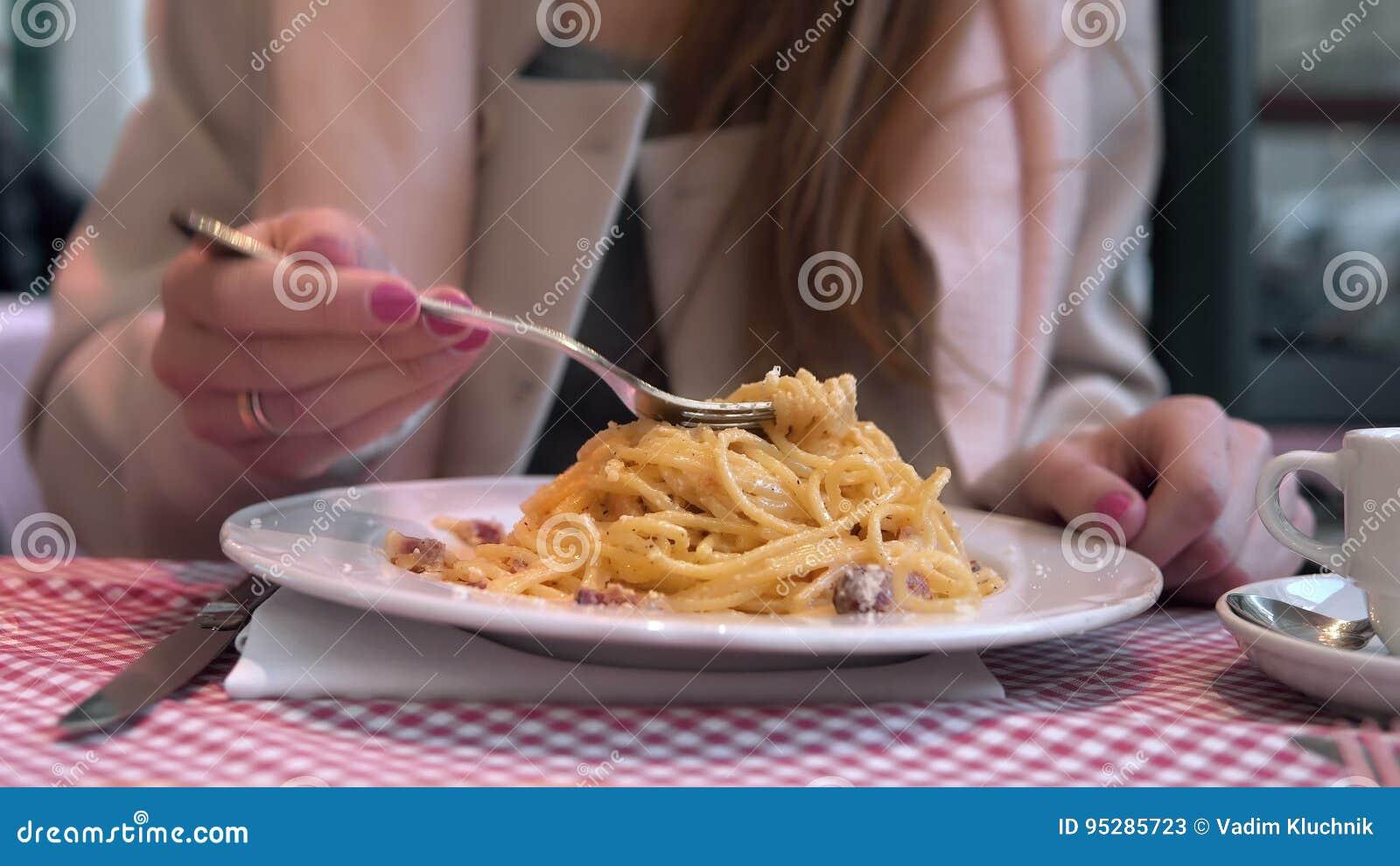 坐在咖啡馆的桌上和享受膳食的年轻愉快的妇女 吃鲜美面团的饥饿的妇女
