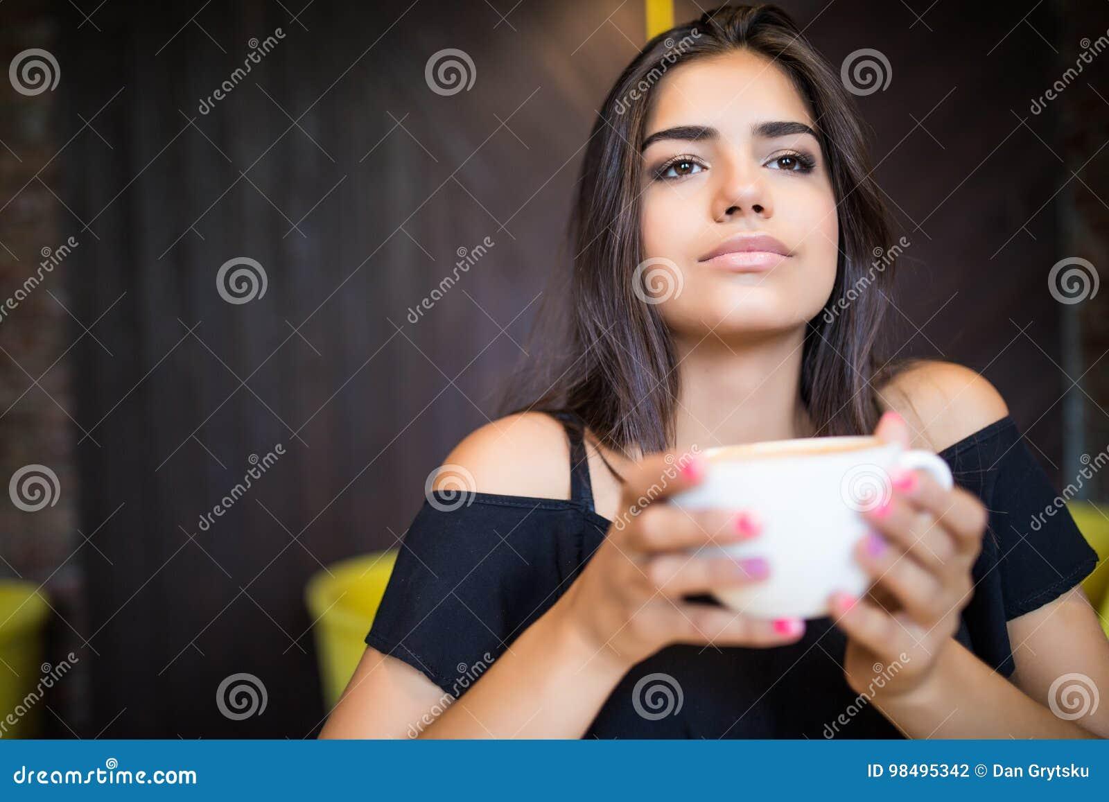 坐在咖啡馆饮用的咖啡的年轻美丽的妇女画象