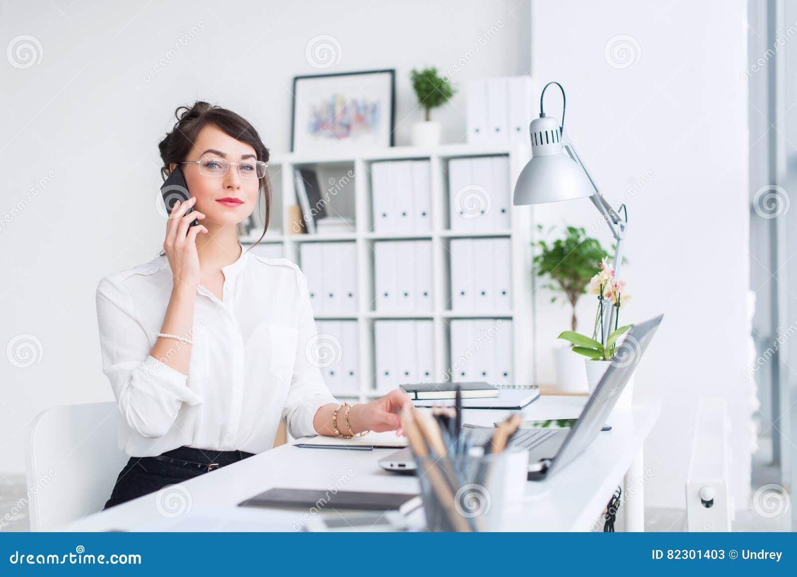 坐在她的工作场所的年轻女实业家,制定出新的企业想法,佩带的正式衣服和玻璃,看