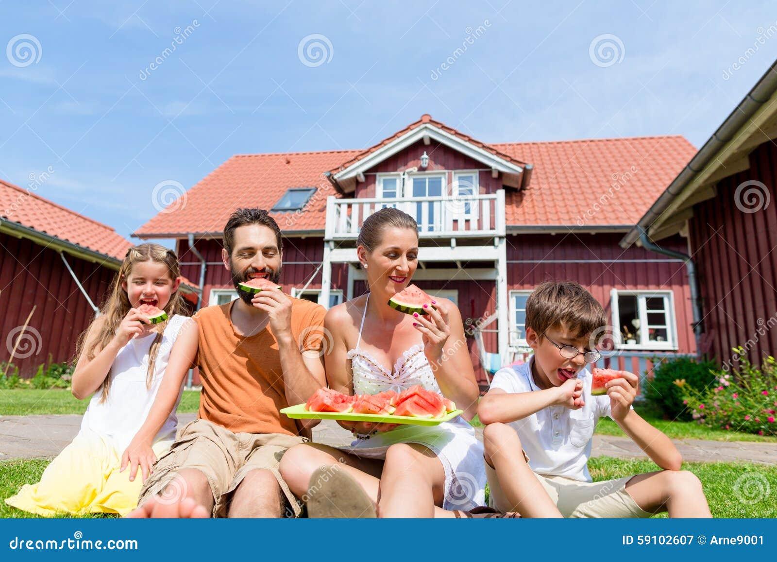 坐在家庭吃西瓜草前面的家庭