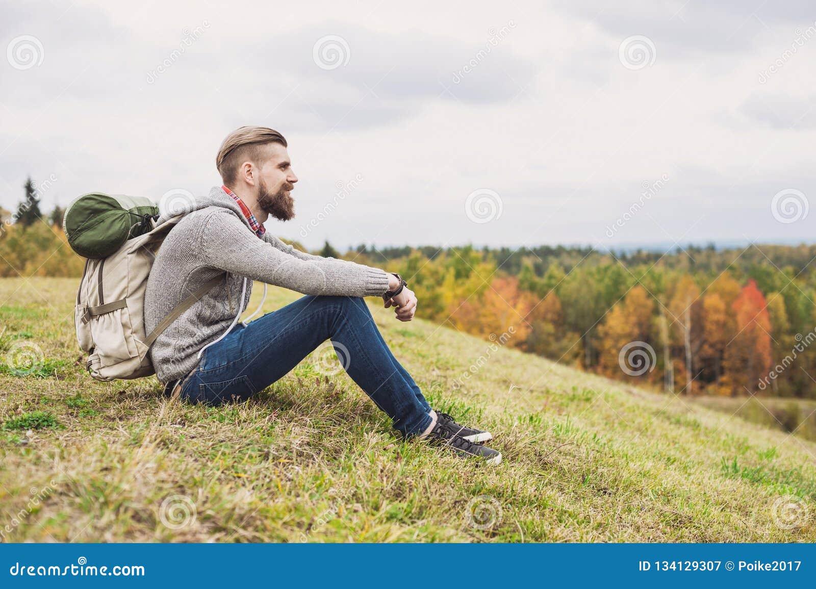 坐在小山顶部的年轻人旅客 旅行和活跃生活方式概念