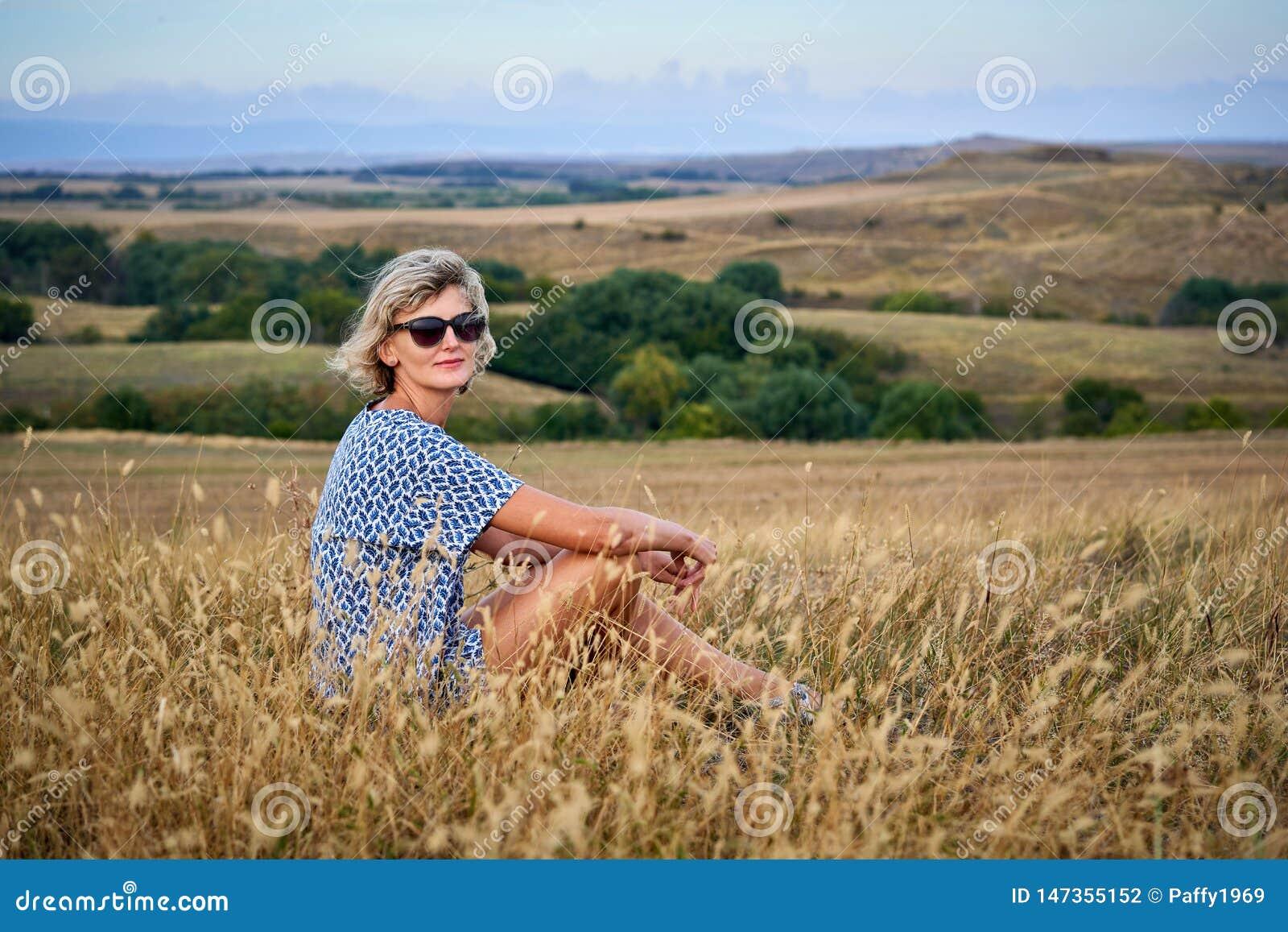 坐在干燥贫瘠草的妇女,看照相机