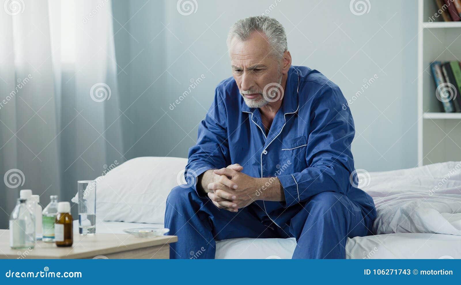 坐在床上和看药片、疗程和医疗保健的哀伤的老人
