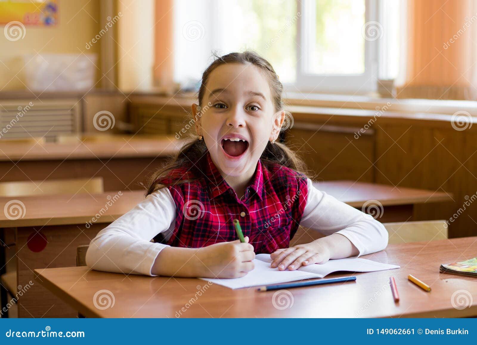 坐在教室和愉快地呼喊的书桌的微笑的白种人女孩 年轻前女小学生画象  愉快的学生