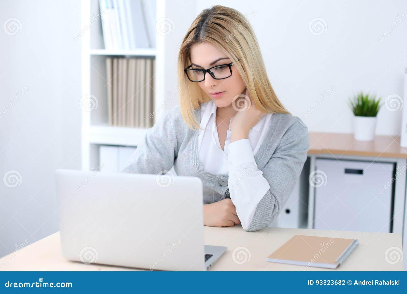 坐在有便携式计算机的办公室工作场所的年轻女商人或学生女孩 家庭企业概念