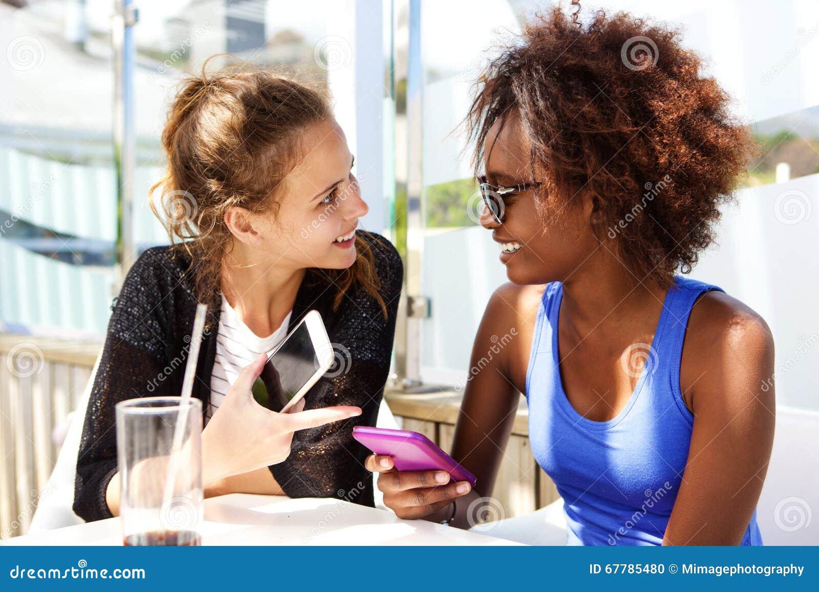 坐在有手机的餐馆的两个朋友