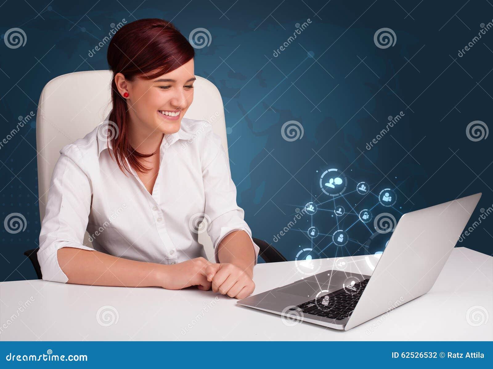 坐在服务台和键入在有社会netw的膝上型计算机的小姐