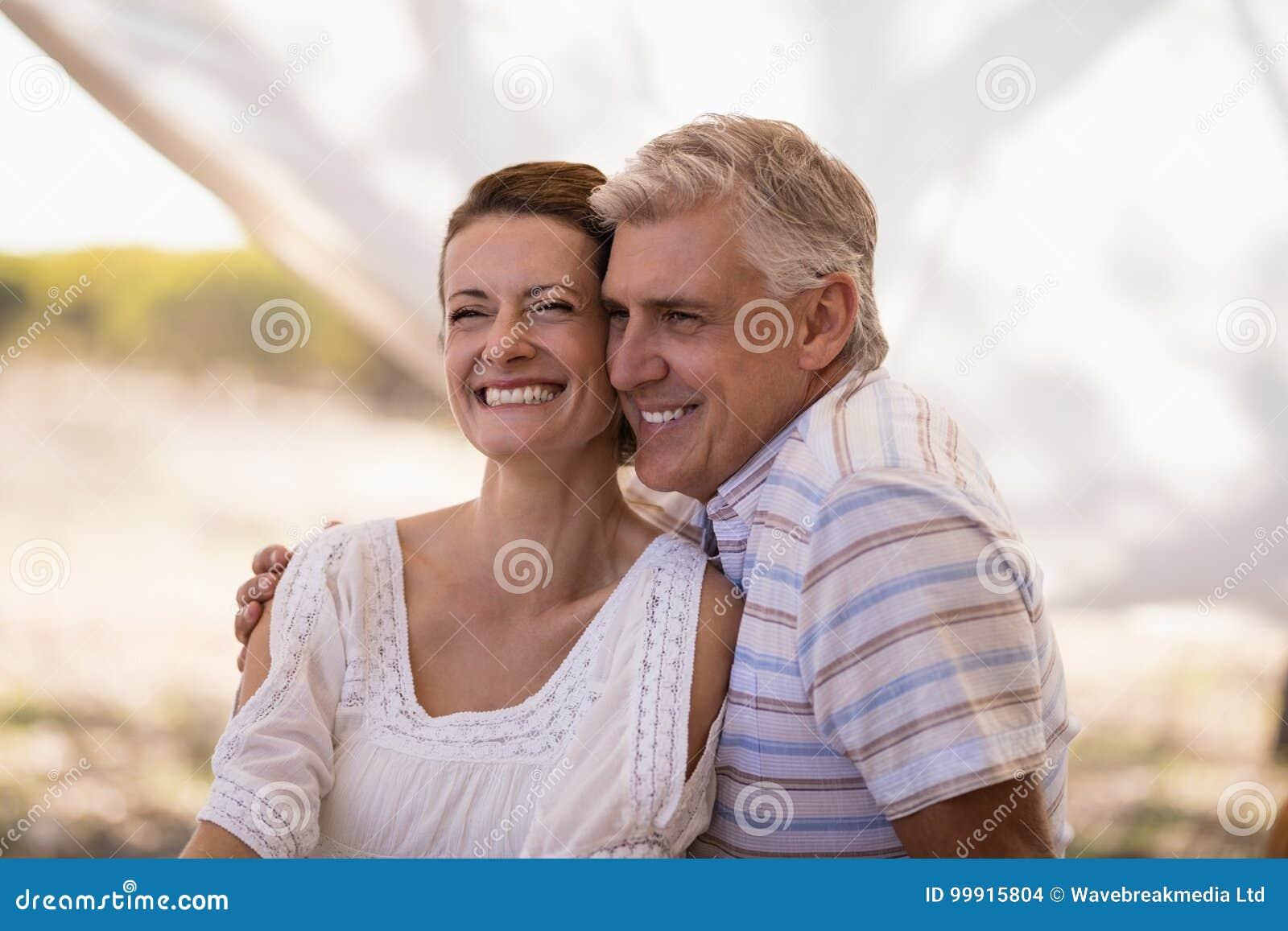坐在村庄的愉快的夫妇