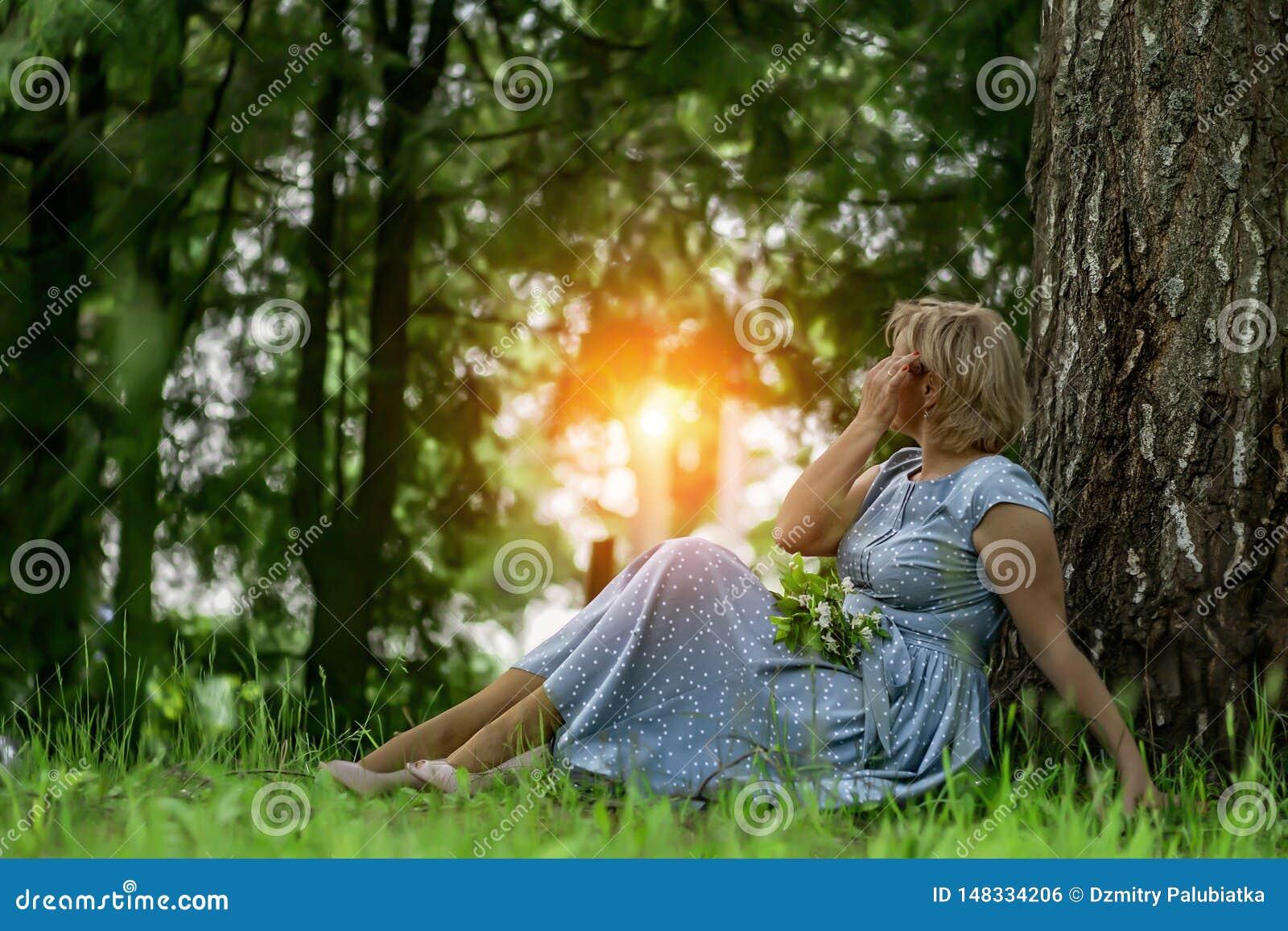坐在树附近的一件蓝色礼服的一名妇女和敬佩日落
