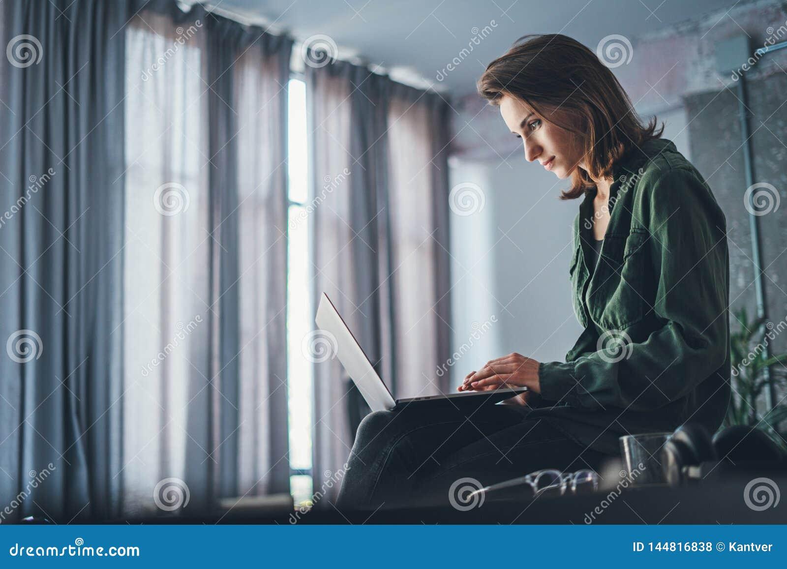 坐在桌上和使用手提电脑的英俊的女性工友 r ??