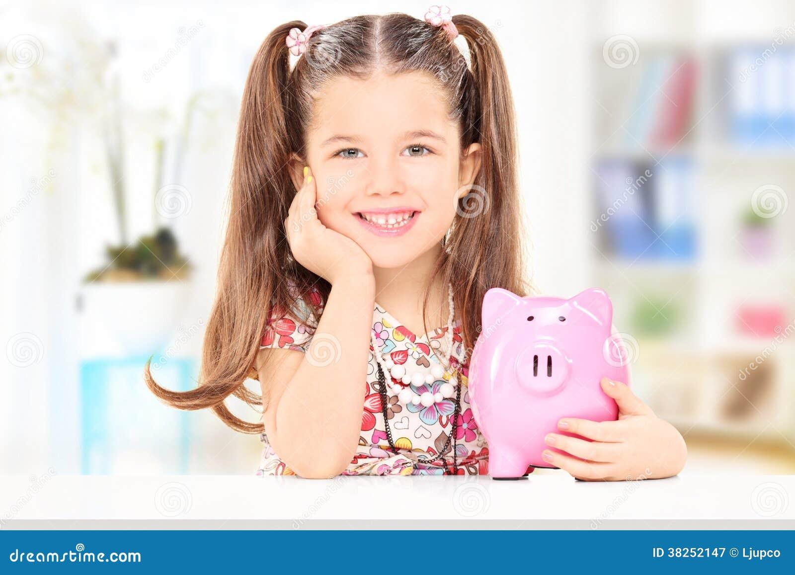 坐在桌上和在家拿着piggybank的逗人喜爱的女孩