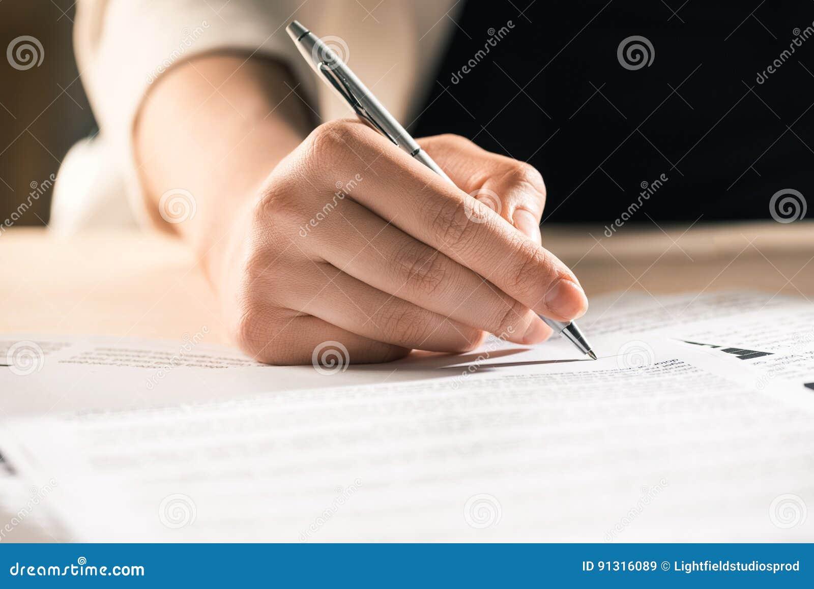 坐在桌上的女实业家签署的合同文件
