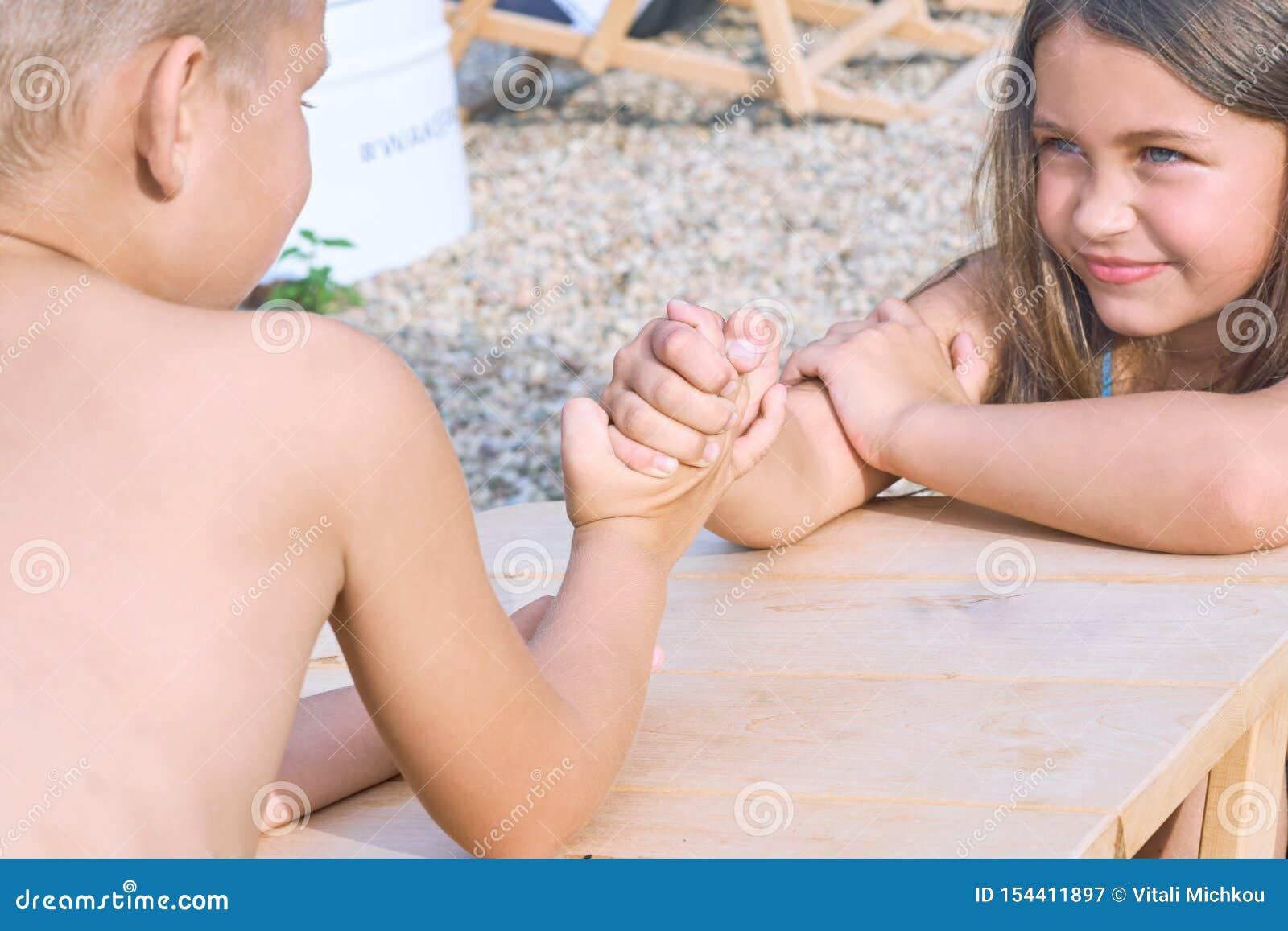 坐在桌上的小男孩和女孩在夏天海滩和武器角力 滑稽的比赛暑假