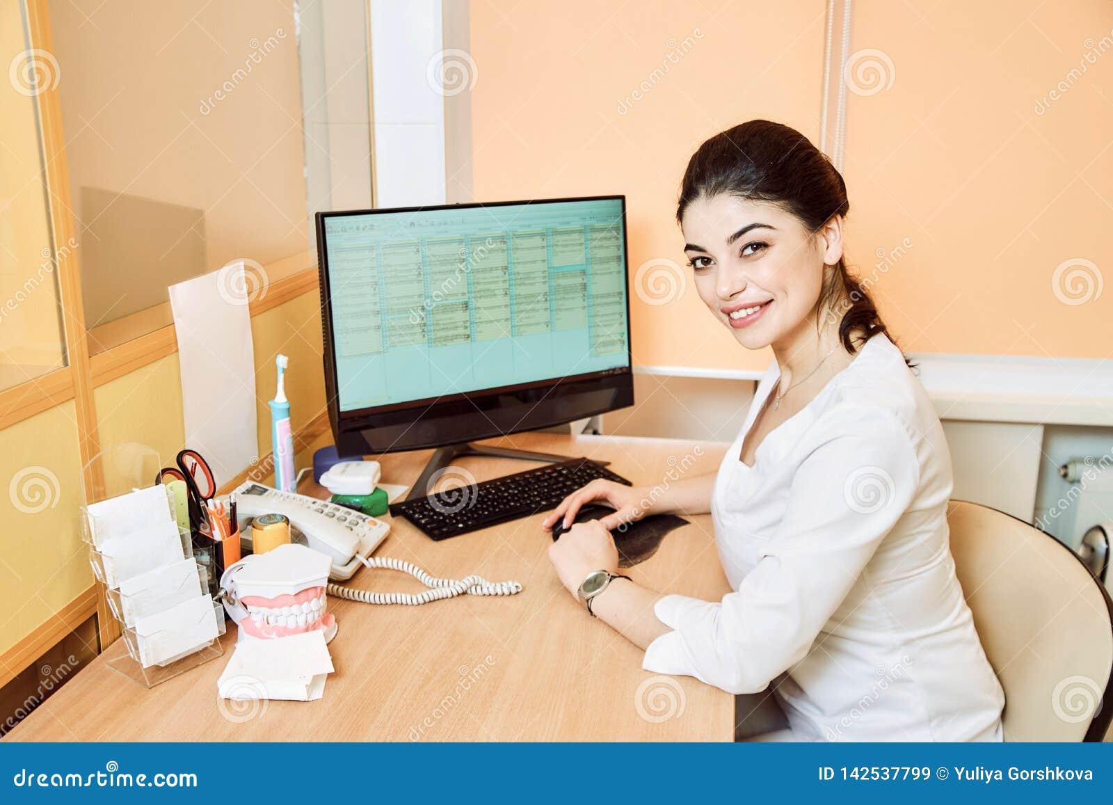 坐在桌上的牙医女孩在计算机和创造一个纪录