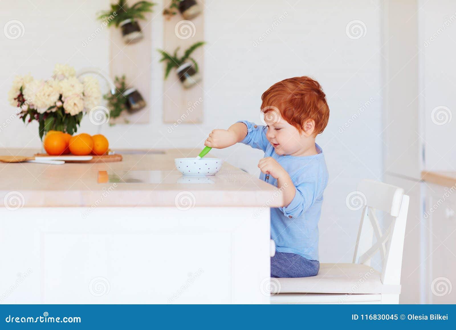 坐在桌上的逗人喜爱的愉快的小孩男婴,吃早餐早晨