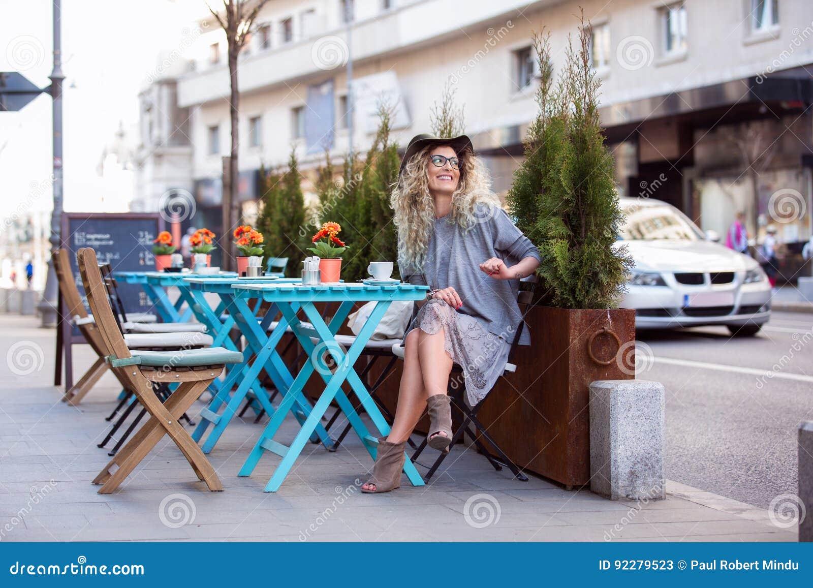 坐在桌outsite和喝杯子的一个美丽的女孩
