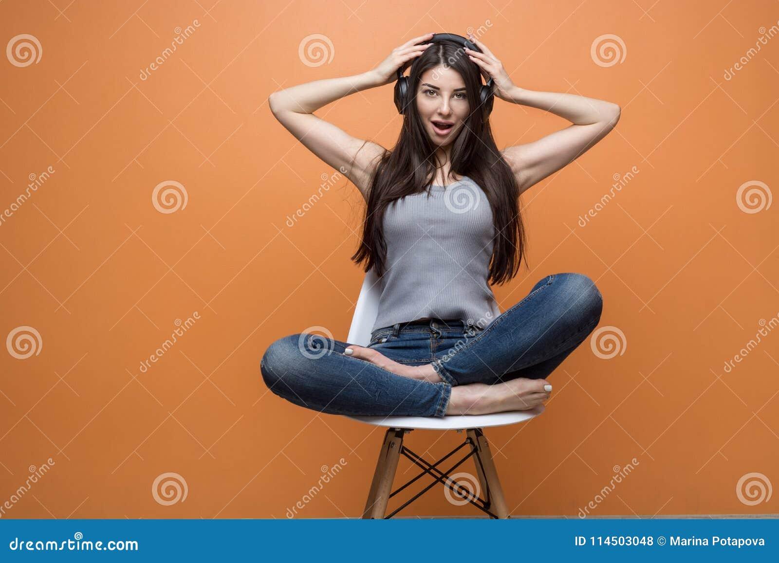 坐在椅子和听到音乐的一个年轻美丽的女孩的画象通过耳机,她的在她的头的手