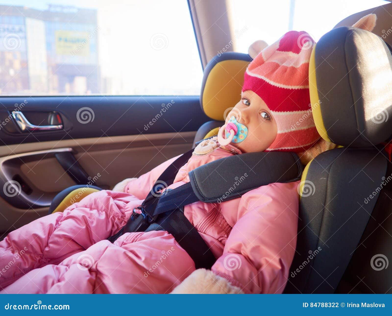 坐在汽车座位的逗人喜爱的小孩女孩画象  儿童运输安全