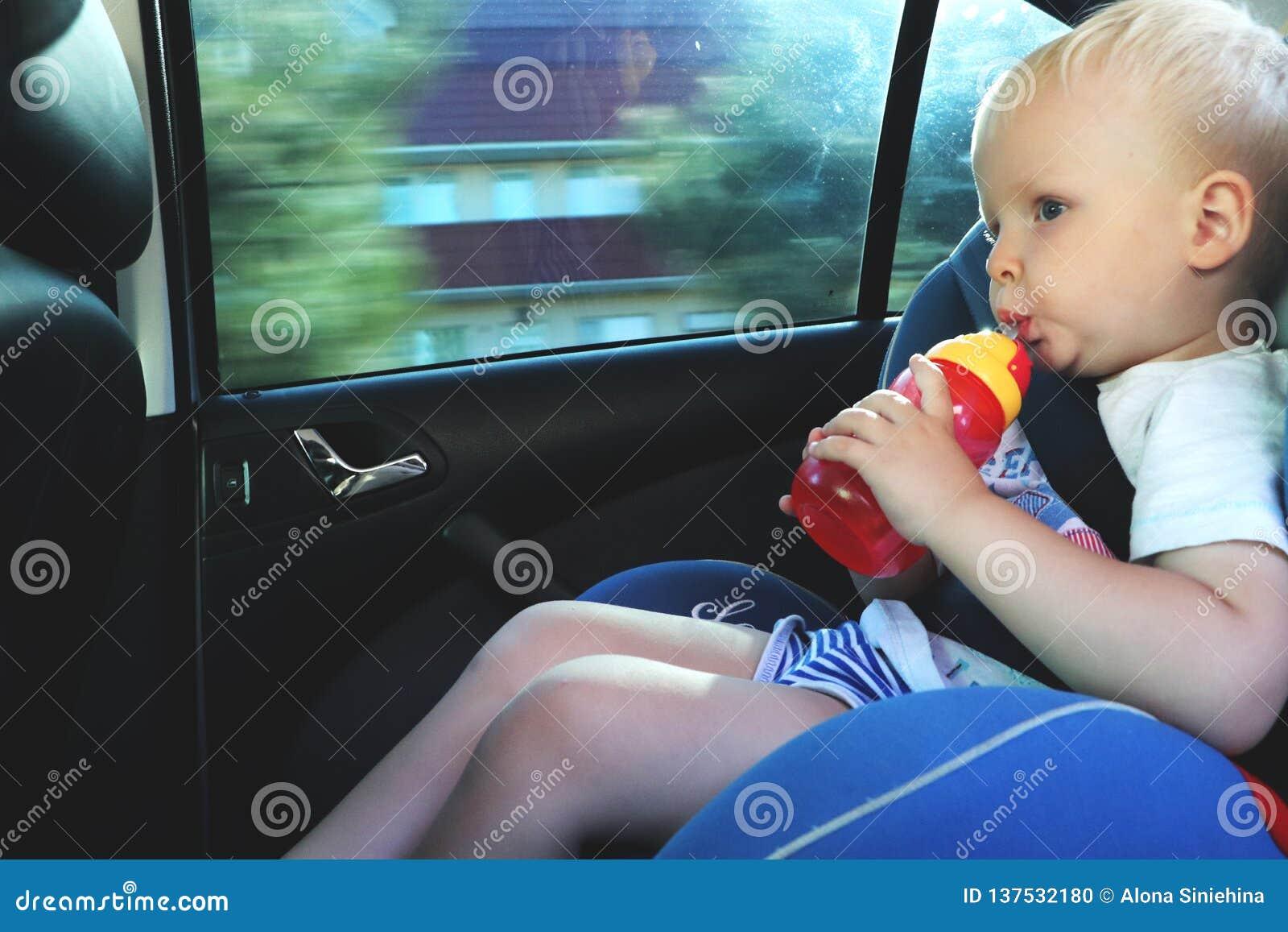 坐在汽车座位的逗人喜爱的小孩男孩画象  儿童运输安全