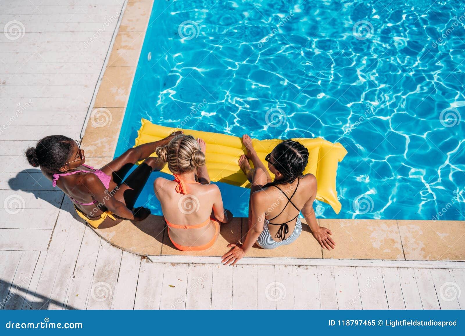 坐在游泳池附近的年轻美丽的不同种族的妇女