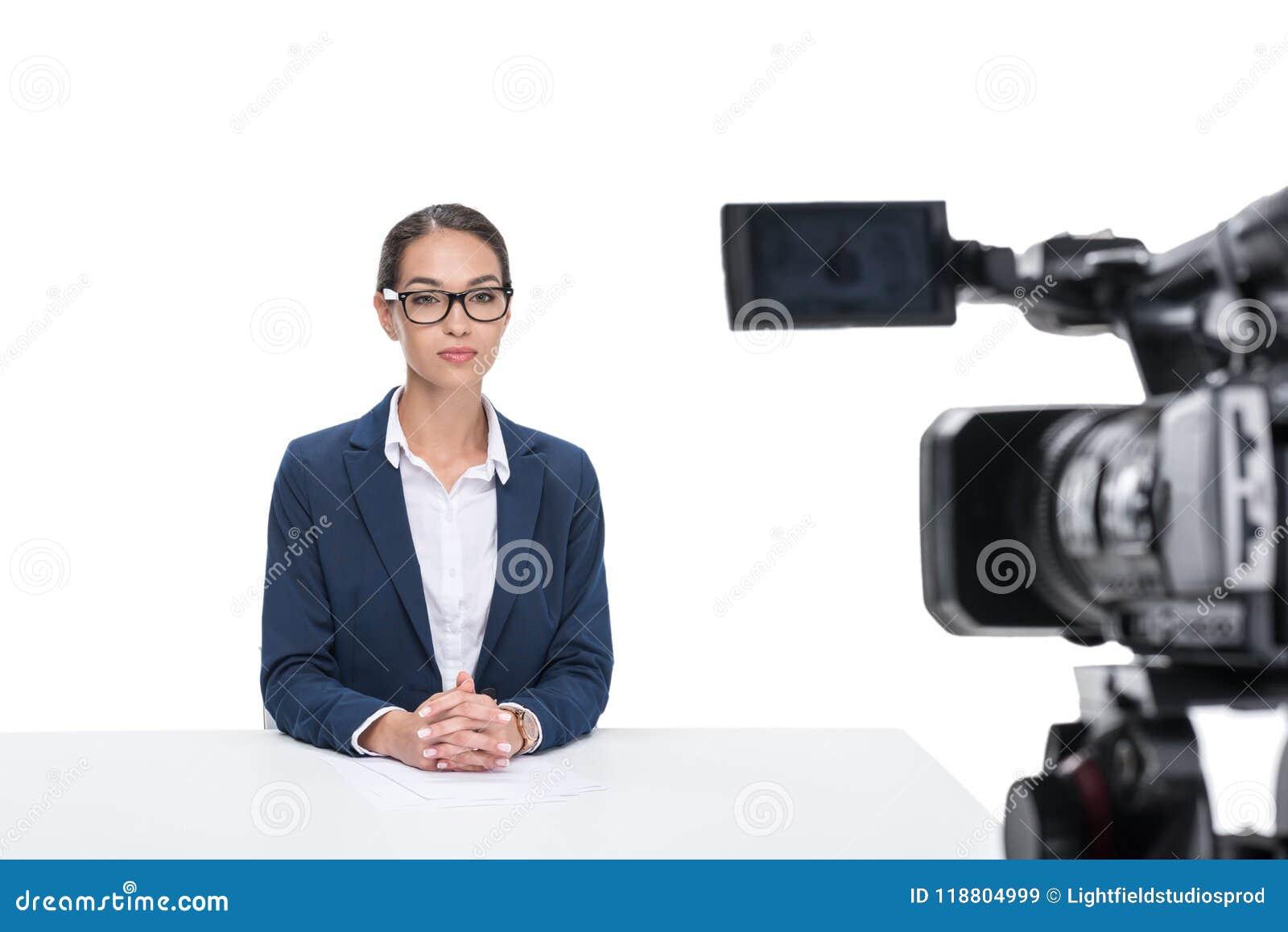 坐在照相机前面的衣服的女性新闻广播员,