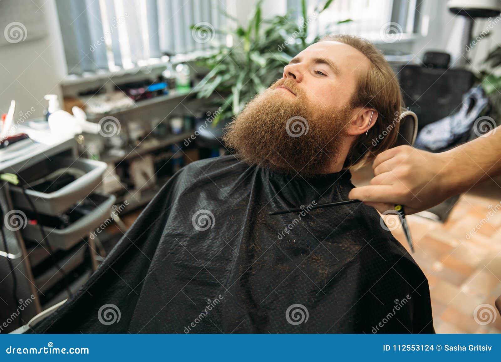 坐在美容院的一把扶手椅子的英俊的年轻有胡子的人