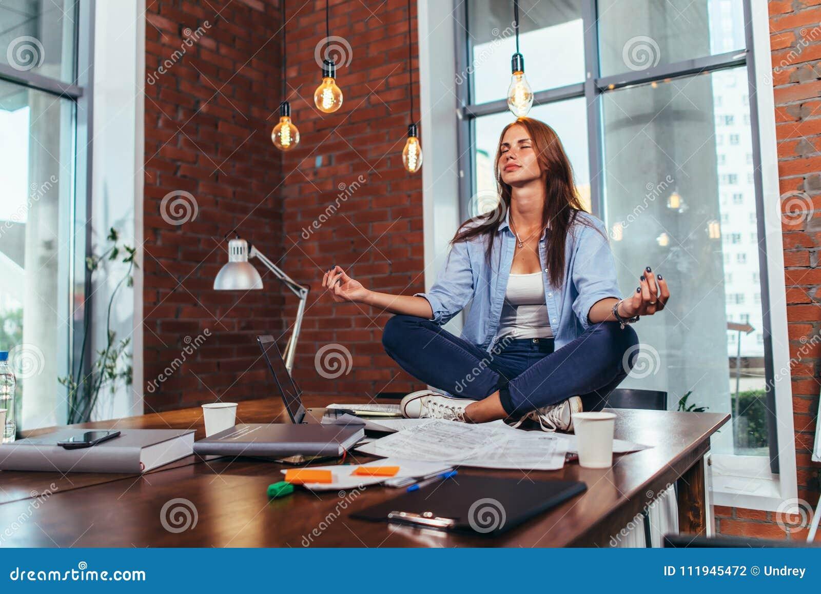 坐在莲花姿势的女学生在桌在她屋子思考的放松里在学习和为检查做准备以后