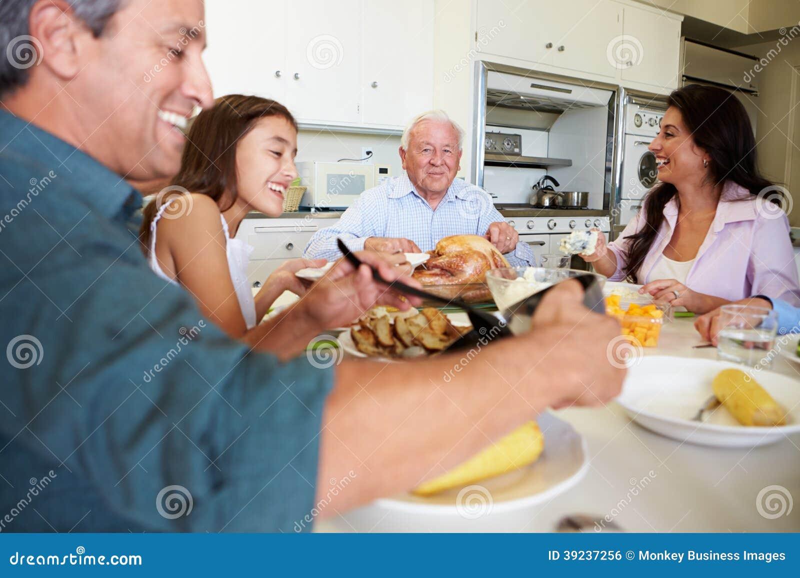 坐在表附近的多代的家庭吃膳食